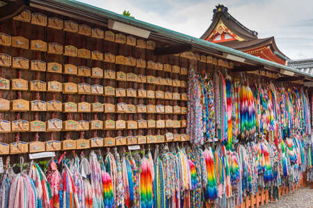 Kyoto, Japan - September 17, 2016: Wall of prayers and wishes left at Fushimi Inari Taisha Shinto Shrine. Wooden boards and colorful strings of origami cranes, each holding a prayer.