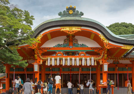Kyoto, Japan - September 17, 2016: People gather in front of the main vermilion shrine at Fushimi Inari Taisha Shinto Shrine. They appeal and pray to the spirits of ancestors. Gray roof with golden trim. Cloudy sky and green trees.