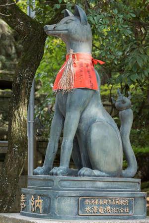 Kyoto, Japan - September 17, 2016: Fushimi Inari Taisha Shinto Shrine. Kitsune, the brown fox, messenger and server of God Inari, has rice strung around its neck and sports a red apron. Against green tree foliage. Editorial