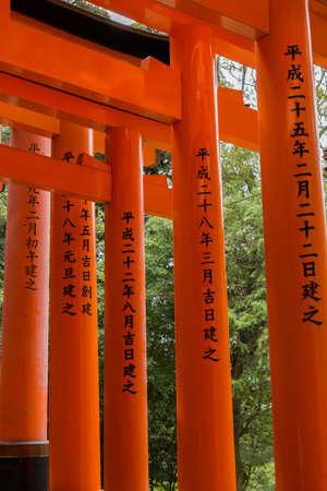 Kyoto, Japan - September 17, 2016: Thousands of Torii create path up the hill at Fushimi Inari Taisha Shinto Shrine. Closeup of some vermilion pillars. Torii with inscriptions on the pillars. Editorial
