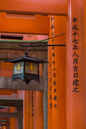 Kyoto, Japan - September 17, 2016: Thousands of Torii create path up the hill at Fushimi Inari Taisha Shinto Shrine. Closeup of some vermilion pillars with one black and golden lantern. Editorial