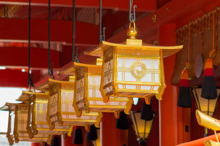 idols: Kyoto, Japan - September 17, 2016: Fushimi Inari Taisha Shinto Shrine. Closeup of a line of golden lanterns hanging off the vermilion ceiling in front of the idols.