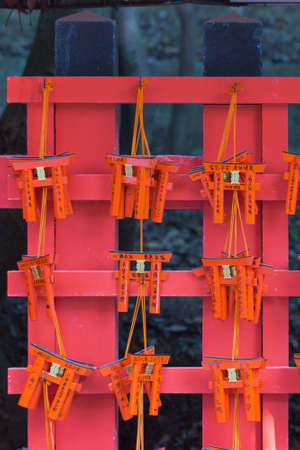 Kyoto, Japan - September 17, 2016: Closeup of nine wooden prayer boards in the shape of Torii at Fushimi Inari Taisha Shinto Shrine. Left by worshipers writing down their wishes and pleas for the spirits of the ancestors.