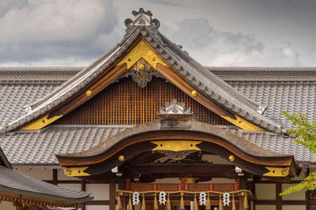 Kyoto, Japan - September 17, 2016: Two different shapes of roof structure at Fushimi Inari Taisha Shinto Shrine. Gray tiles, brown facial boards and golden trim under cloudy skies. Editorial