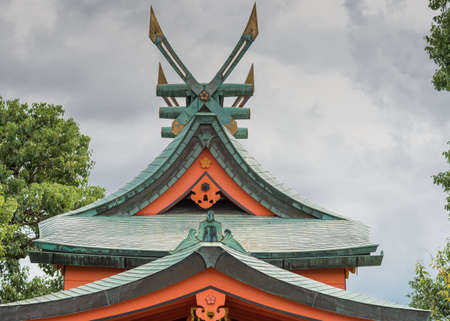 Kyoto, Japan - September 17, 2016: Windmill like roof structure at Fushimi Inari Taisha Shinto Shrine. Green tiles, red facial boards, cloudy sky, fixed gold tipped wings.