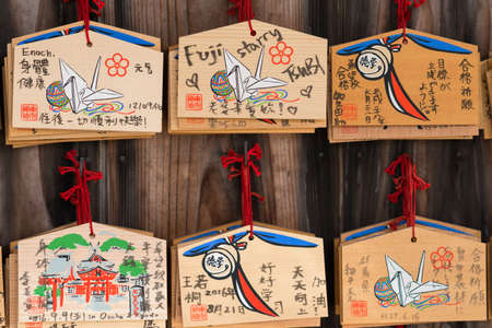 Kyoto, Japan - September 17, 2016: Closeup of six wooden prayer boards at Fushimi Inari Taisha Shinto Shrine. Left by worshipers writing down their wishes and pleas for the spirits of the ancestors.
