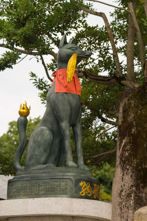 Kyoto, Japan - September 17, 2016: Fushimi Inari Taisha Shinto Shrine. Kitsune, the bronze fox, messenger and server of God Inari, holds rice stalks in its mouth and sports a red apron. Against green tree foliage and gray skies.