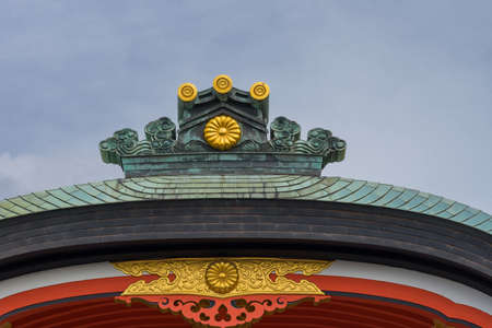 Kyoto, Japan - September 17, 2016: Fushimi Inari Taisha Shinto Shrine. The crest of a roof shines in bronze and gold against a blue sky, above vermilion facial board.