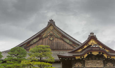 Kyoto, Japan - September 19, 2016: The roof structure of the Ninomaru Palace buildings at Nijo Castle. Two roof crests are different since one is recently repainted and its gold plates polished. Cloudy sky, couple of trees.