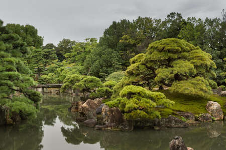 Kyoto, Japan - September 19, 2016: View on part of the garden of Ninomaru Palace at Nijo Castle. Pond, rocks, trees and a small bridge. Cloudy sky.