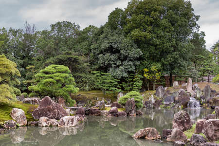 Kyoto, Japan - September 19, 2016: View on part of the garden of Ninomaru Palace at Nijo Castle. Pond, rocks, trees.