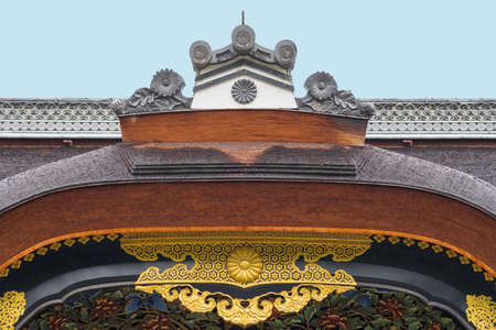 Kyoto, Japan - September 19, 2016: The central crest of the Kara-Mon gate at the Nijo Castle shows a wooden bow, golden trim and wood carvings under a light blue sky. Editorial