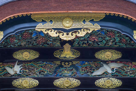 Kyoto, Japan - September 19, 2016: Closeup of wood carving at Kara-mon gate in Nijo Castle. Flowers, butterflies, cranes, insects and golden decorations. Editorial