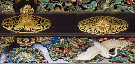 Kyoto, Japan - September 19, 2016: Closeup of wood carving at Kara-mon gate in Nijo Castle. Crane and golden decorations.