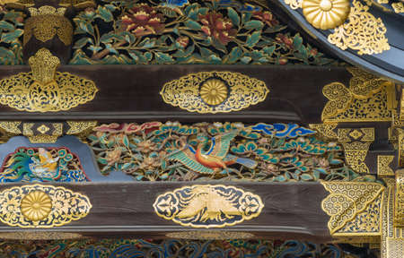 Kyoto, Japan - September 19, 2016: Closeup of wood carving at Kara-mon gate in Nijo Castle. Shows a colorful bird, a man struggling with a dragon and golden decorations.