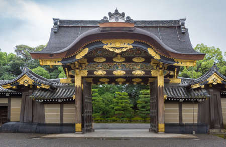 Kyoto, Japan - September 19, 2016: Majestic Kara-mon gate at the Nijo Castle. Plenty of gold trimmings and colorful woodwork. Cloudy sky and green foliage in background.