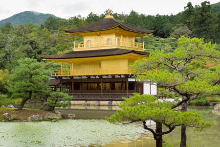 Kyoto, Japan - September 19, 2016: The golden temple of Kinkaku-ji stands behind pond and in front of jungle trees.