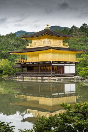 Kyoto, Japan - September 19, 2016: The golden temple of Kinkaku-ji stands behind pond and in front of jungle trees. Portrait composition. Temple is entirely reflected in the pool. Editorial