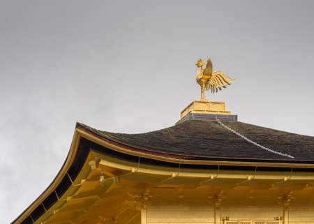 Kyoto, Japan - September 19, 2016: The golden temple of Kinkaku-ji. On top stands the image of the phoenix. Roof and the golden statue against dark sky.