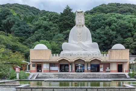 Kyoto, Japan - September 19, 2016: The Ryozen Kannon WW II Memorial shrine is set against forested hills. The giant statue of goddess Kannon dominates a documentation center.