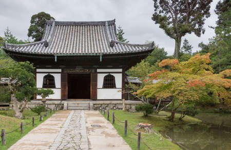 Kyoto, Japan - September 19, 2016: Smaller hall of the Kodai-ji Buddhist Temple complex sits in a beautiful garden which starts to show autumn colors. Gray sky.