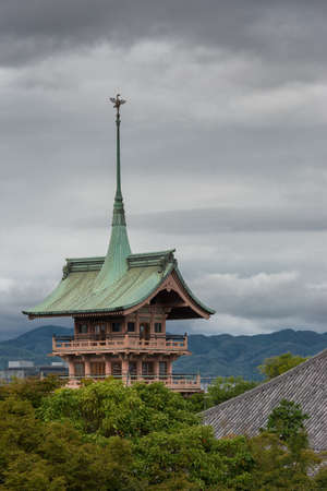 Kyoto, Japan - September 19, 2016: The pagoda of Daiunin Buddhist temple towers over trees under cloudy sky. The Phoenix stands on top of sharp, long, green peak and roof. Hills and jungle in background.