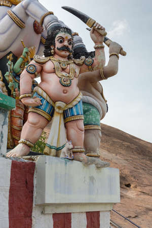 Madurai, India - October 21, 2013: Statue of belligerent Karuppana Sami in front of a horse. He loos hostile and swings a big knife. All colorful statues at his shrine near Nagamalai village.
