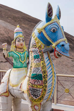 Madurai, India - October 21, 2013: Statue of young woman sitting of horse. She has no legs. Beige mountain rock as background. All colorful statues at his shrine of Karuppana Sami near Nagamalai village.