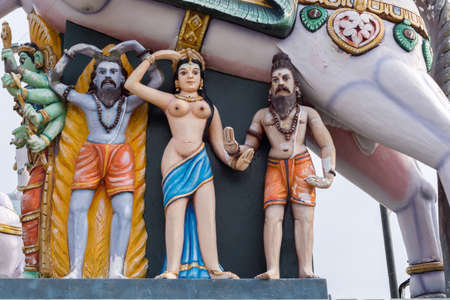 Madurai, India - October 21, 2013: Under the belly of a horse stand a half-naked, young woman and two bearded men.  All colorful statues at the shrine of Karuppana Sami near Nagamalai village.