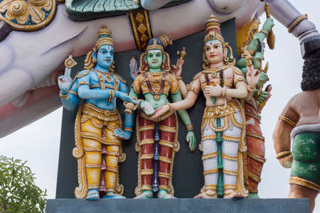 Madurai, India - October 21, 2013: Under the belly of a horse is the wedding between Meenakshi and Shiva reenacted with the help of Vishnu. All colorful statues at Karuppana Sami shrine near Nagamalai.