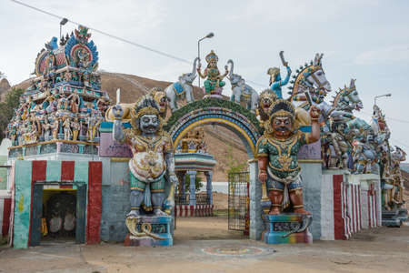 Madurai, India - October 21, 2013: Two copies of Karuappan Sami guard the entrance to their shrine. Lakshmi is present on top of the gate. Horses, strong men, Vimanam of sanctuary and more statues.