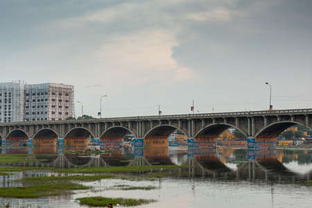 Madurai, India - October 22, 2013: Morning photo of highway 85 bridge into Madurai over the Vaigai River. Bows of bridge reflected in water. Colorful advertisements. Large building under construction with scaffold.