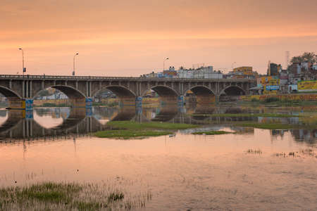 Madurai, India - October 22, 2013: Early morning photo of highway 85 bridge into Madurai over the Vaigai River. Bows of bridge reflected in water. Orange-yellow sky reflected in water. Billboards.