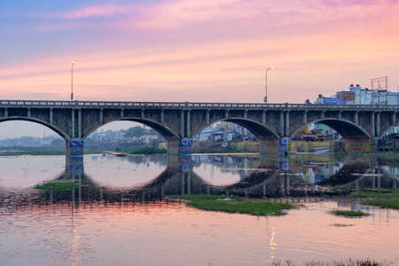 Madurai, India - October 22, 2013: Early morning photo of highway 85 bridge into Madurai over the Vaigai River. Bows of bridge reflected in water. Blue, purple sky reflected, too. Billboards.
