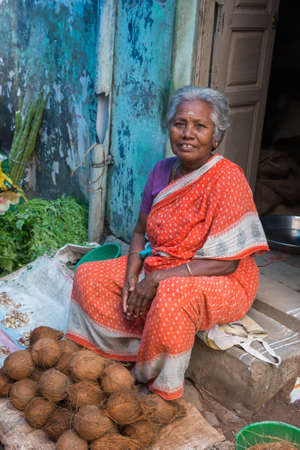graying: Madurai, India - October 22, 2013: An older graying woman in red sari sells a handful of coconuts sitting on her doorstep. Blue wall.