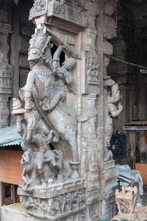 nagara: Madurai, India - October 22, 2013: Historic gray-stone statue of Nayak king on his horse in attacking mode. On pillar at entrance of Nagara Mandapam. Editorial