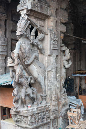 Madurai, India - October 22, 2013: Historic gray-stone statue of Nayak king on his horse in attacking mode. On pillar at entrance of Nagara Mandapam. Editorial