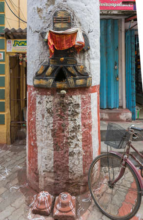 Madurai, India - October 22, 2013: Ten pillars of the Nayak palace remain in downtown. On one, a colorful image of shivalingam has been chiseled. Bike and shop doors in photo, too.