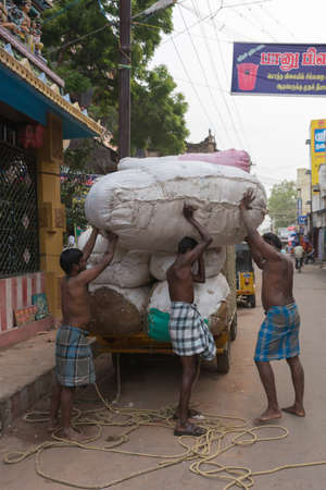 unload: Madurai, India - October 22, 2013: Three half-naked men unload huge cotton bales from a small truck. Two men are helping the third man to put the bale on his back. Editorial