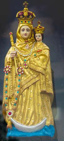 Vadipatti, India - October 22, 2013: Closeup of golden Virgin Mary statue at Vadipatti Arockia Annai Shrine. She holds baby jesus. Both wear a crown. Slim crescent moon present. Plenty of jewels.