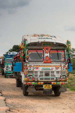 Vadipatti, India - October 22, 2013: Over decorated, colorful, heavy, Tata truck parked along the way in the dirt. Driver inside. Partly covered windscreen. Rainy sky.