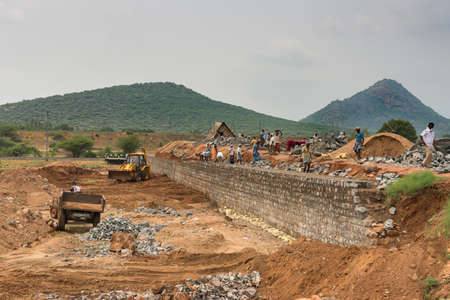 tamil nadu: Dindigul, India - October 22, 2013: Large number of people build a stone dam mostly with manual labor in the Dindigul region of Tamil Nadu. A bulldozer and truck in picture. Green hill and gray sky.