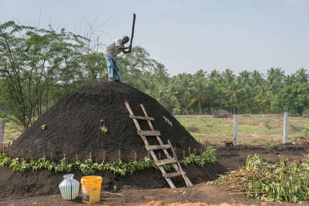 Dindigul, India - October 22, 2013: A man on top of his charcoal hill of black earth which covers raw wood. The man fastens the black dirt by hammering it with a beam. The ancient way. Blue sky and green background.
