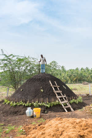 fastens: Dindigul, India - October 22, 2013: A man on top of his charcoal hill of black earth which covers raw wood. The man fastens the black dirt by hammering it with a beam. The ancient way. Blue sky and green background.