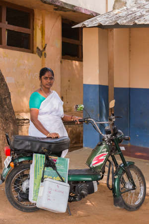 inoculate: Dindigul, India - October 22, 2013: A public funded nurse swings by preschool to inoculate a kid with a polio shot. She wears white sari. Her fridge box hangs on motorcycle. School building background. Editorial