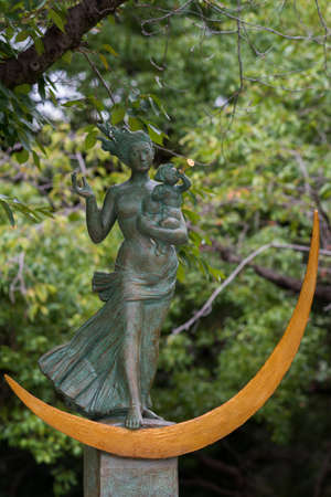eradication: Hiroshima, Japan - September 20, 2016: Madonna image, mother holding child, standing on golden moon, is the Prayer for Peace statue at the Hiroshima Peace Memorial Park. Green foliage as background.