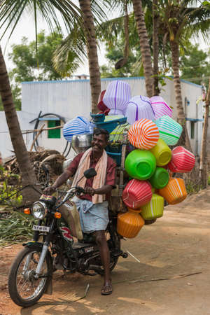 Dindigul, India - October 22, 2013: A smiling man, an ambulant vendor, drives up on his motorcycle at a rural village. The bike is overloaded with colorful, plastic, jars the size of five to ten liters.