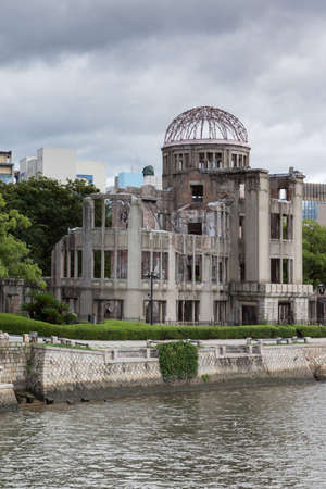 eradication: Hiroshima, Japan - September 20, 2016: Ruin of Hiroshima Prefectural Industrial Promotion Hall has become the A-Bomb Memorial in Hiroshima. One of the few buildings with some walls left erect. River in front, cloudy sky.