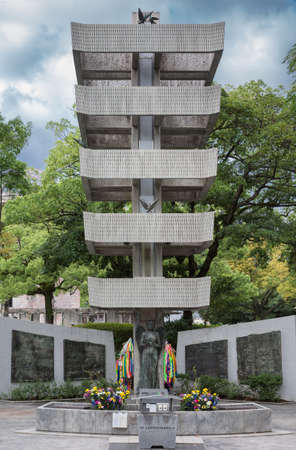 mobilization: Hiroshima, Japan - September 20, 2016: Memorial tower and murals to the Mobilized Students in the Memorial Peace Park of Hiroshima. Pagoda style building, female figure, pigeons, origami, crane, flowers.