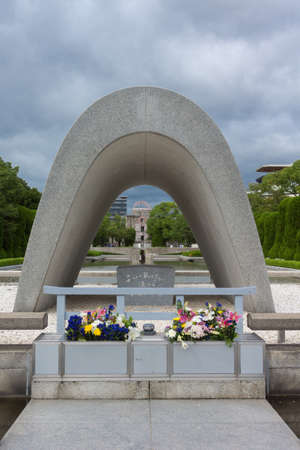eradication: Hiroshima, Japan - September 20, 2016: The Memorial Cenotaph with the A-bomb ruin memorial at the far end it the Peace Memorial Park, looking over the pool and eternal flame. Flowers and cloudy sky.